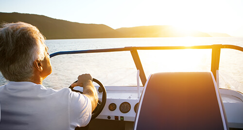Marine Audio: Older gentleman driving a speed boat with a windsheild and upgraded device dash